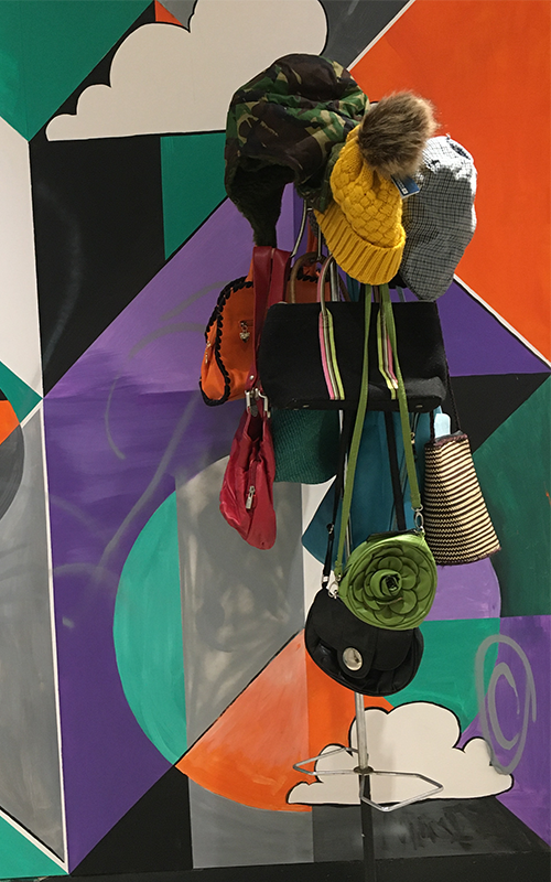 Colourful hats and bags on a stand in front of a mural